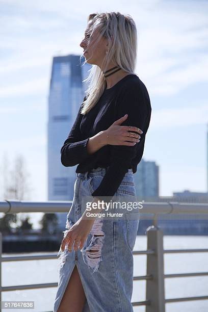 Emily Mercer wearing high waisted ripped One Teaspoon denim skirt Rag Bone navy sweater Alison Lou choker necklace right hand rings by Zoe Chicco...