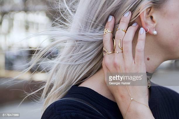 Emily Mercer wearing Rag Bone navy sweater Alison Lou choker necklace with heart eyes emoji pendant Maria Tash silver hoop earring Mizuki pearl...