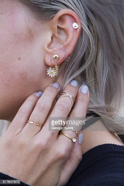Emily Mercer wearing Rag Bone navy sweater Alison Lou choker necklace daisy drop earring sad face emoji stud earring and happy face emoji earring...