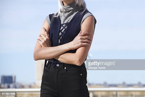 Emily Mercer wearing vintage grey turtleneck sleeveless sweater blue Urban Outfitters navy top with tie black high waisted BLK DNM pants left hand...