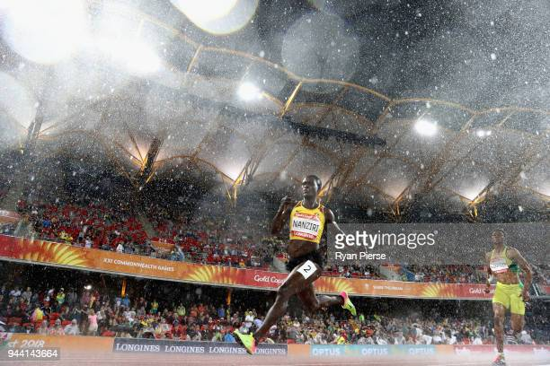 Emily Nanziri of Uganda competes in the rain during the Women's 400 metres semi finals during the Athletics on day six of the Gold Coast 2018...