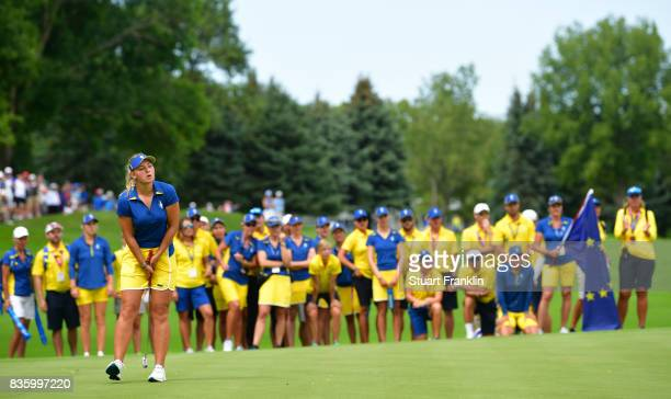 Emily Pedersen of Team Europe reacts to a putt whilst being watched by her team during the final day singles matches of The Solheim Cup at Des Moines...