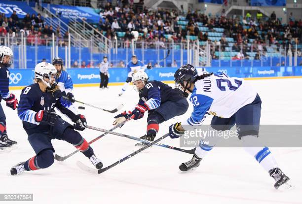 Emily Pfalzer and Hilary Knight of the United States Vietnam for the puck with Emma Nuutinen of Finland during the Ice Hockey Women Playoffs...