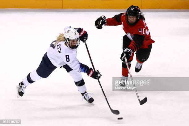 Emily Pfalzer of the United States shoots against Blayre Turnbull of Canada during the Women's Ice Hockey Preliminary Round Group A game on day six...