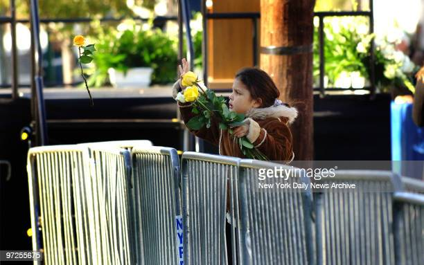 Emily Sanchez who lost her father, Elvis Sanchez, tosses yellow roses over a barricade onto the lawn of a house built at the crash site during a...
