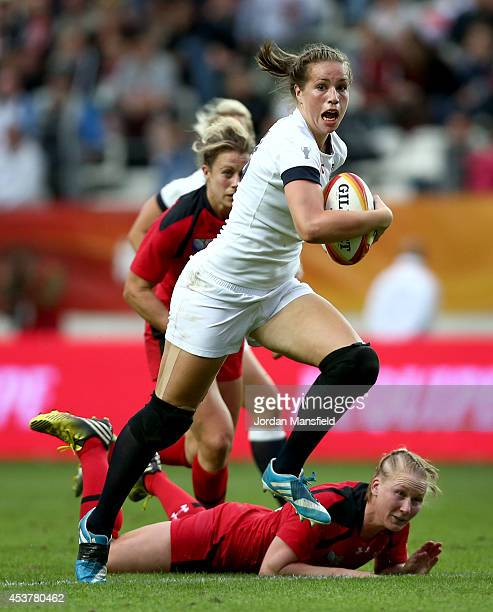 Emily Scarratt of England breaks free of a challenge from Mandy Marchak of Canada during the IRB Women's Rugby World Cup 2014 Final between England...