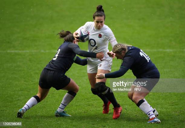 Emily Scarratt of England runs with the ball while challenged by Lisa Thomson of Scotland and Molly Wright of Scotland during the Women's Six Nations...