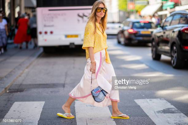Emily Sindlev wearing Dior saddle bag yellow button shirt striped skirt flip flops seen outside Mykke Hofmann during the Copenhagen Fashion Week...