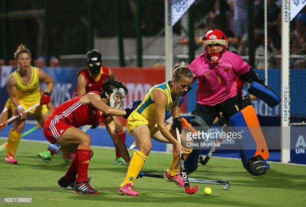Emily Smith of Australia is watched by Qiong Wu and goalkeeper Dongxiao Li of China during the Pool B match between Australia and China on day one of...