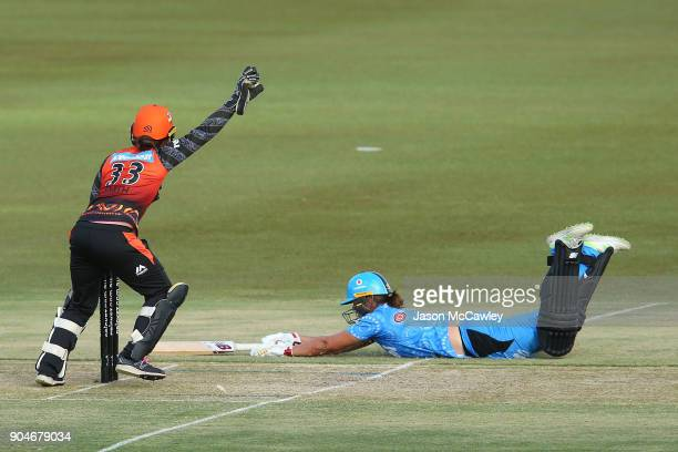 Emily Smith of the Scorchers attempts to run out Suzie Bates of the Strikers during the Women's Big Bash League match between the Perth Scorchers and...