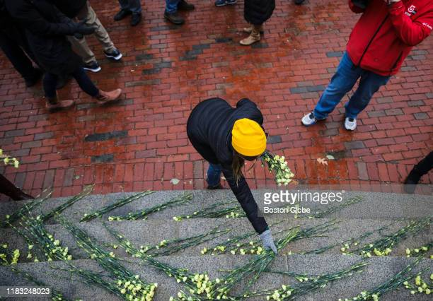 Emily Stein president of the Safe Roads Alliance places yellow flowers on the steps of the Massachusetts State House in Boston during the World Day...