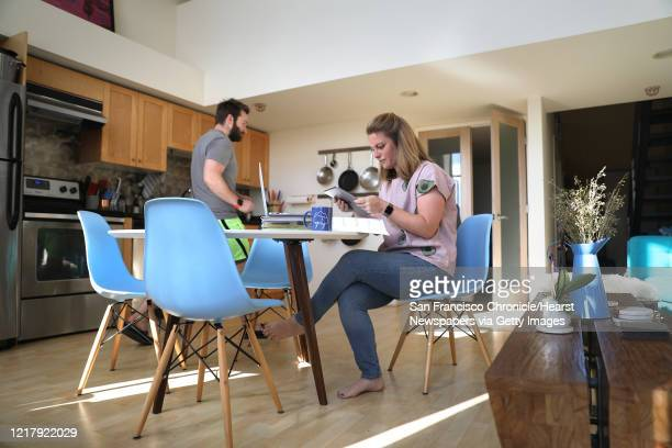 Emily Storms gets ready to teach her fifth grade math class on her kitchen table at home via Zoom as her boyfriend Sean Moore passes by in the...