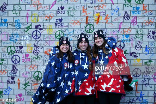 Emily Sweeney Erin Hamlin and Summer Britcher of the United States pose in front of the Truce Wall after the team's flag raising ceremony during...