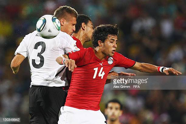 Emir Dilaver of Austria jumps for a header with Ahmed Hassan and Mohamed Ibrahim of Egypt during the FIFA U20 World Cup 2011 group E match between...