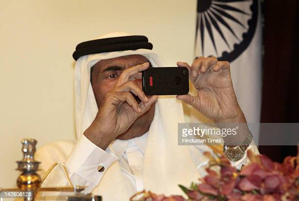 Emir of Qatar Sheikh Hamad bin Khalifa Al Thani uses his phone to take a video of the signing of agreements at Hyderabad house on April 9 2012 in New...