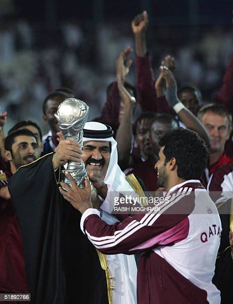Emir of Qatar Sheikh Hamad bin Khalifa AlThani hands the 17th Gulf Cup with to Qatari palyer Amer AlKaabi after the victory against Oman during the...