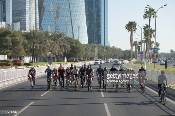 Emir of Qatar Sheikh Tamim bin Hamad Al Thani rides a bicycle with a group of youth during an exhibition as part of Qatar National Sport Day in Doha,...