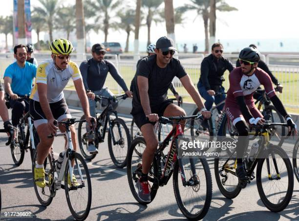 Emir of Qatar Sheikh Tamim bin Hamad Al Thani rides a bicycle with a group of youth during an exhibition as part of Qatar National Sport Day in Doha...