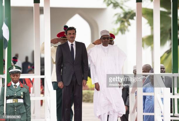 Emir of Qatar Sheikh Tamim bin Hamad alThani and President of Nigeria Muhammadu Buhari stand in silence during an official welcoming ceremony in...