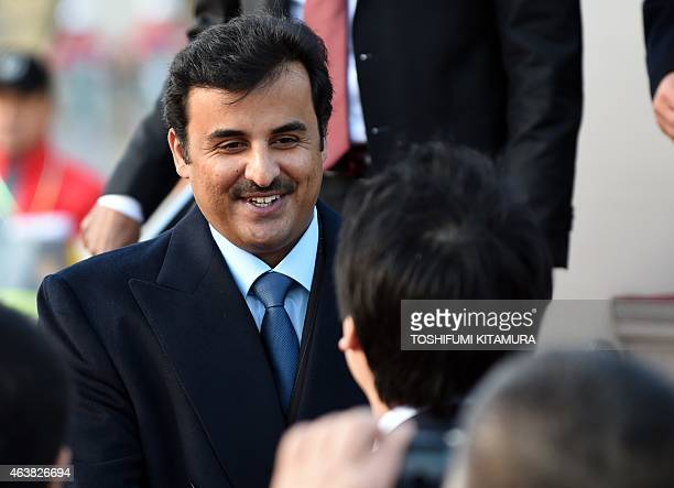Emir of Qatar Sheikh Tamim bin Hamad AlThani greets wellwishers upon his his arrival at the Haneda International airport in Tokyo on February 19 2015...