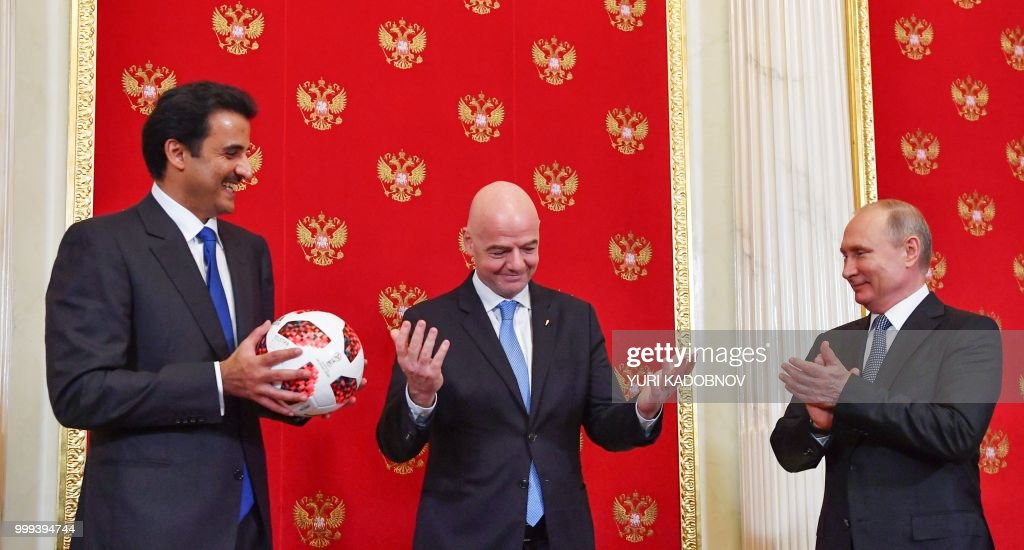 Emir of Qatar Sheikh Tamim bin Hamad Al-Thani (L) holds a ball as Russian President Vladimir Putin (R) and FIFA President Gianni Infantino (C) react during a symbolic transfer of the authority to Qatar to host the World Cup 2022 at the Kremlin in Moscow on July 15, 2018.
