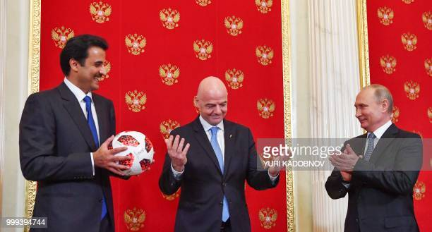 Emir of Qatar Sheikh Tamim bin Hamad AlThani holds a ball as Russian President Vladimir Putin and FIFA President Gianni Infantino react during a...