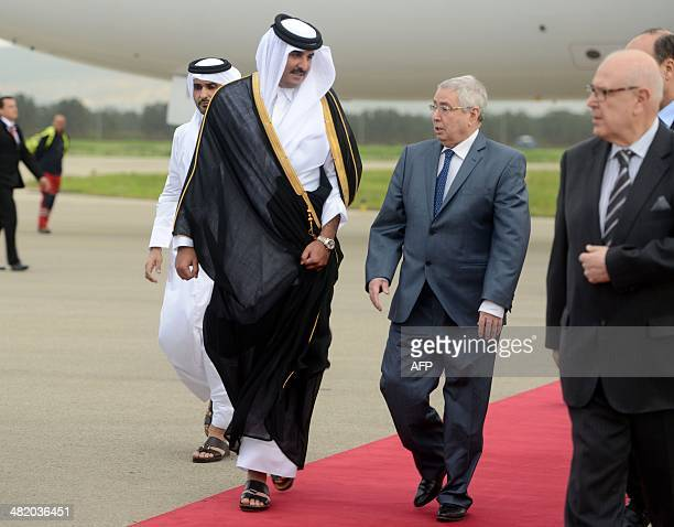 Emir of Qatar Sheikh Tamim bin Hamad AlThani is greeted by Algerian Speaker of the Council of the Nation Abdelkader Bensalah upon his arrival at...