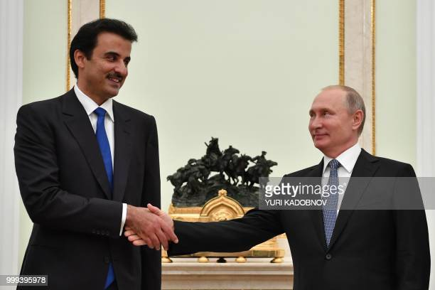 Emir of Qatar Sheikh Tamim bin Hamad AlThani shakes hands with Russian President Vladimir Putin during their meeting at the Kremlin in Moscow on July...