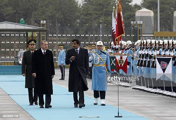 Emir of Qatar Sheikh Tamim bin Hamad bin Khalifa Al Thani and Turkish President Recep Tayyip Erdogan walk past a guard of honor during an official...