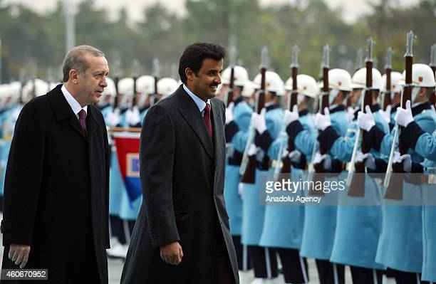 Emir of Qatar Sheikh Tamim bin Hamad bin Khalifa Al Thani and Turkish President Recep Tayyip Erdogan walk past a guard of honor during an official...