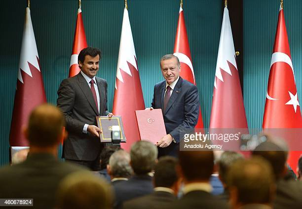 Emir of Qatar Sheikh Tamim bin Hamad bin Khalifa Al Thani and Turkish President Recep Tayyip Erdogan shake hands after they signed political...