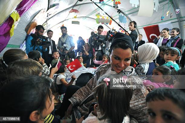 Emir of Qatar Sheikh Tamim's mother Sheikha Mozah listens Syrian children at a classroom during his visit to the Syrian Refugee Camp with Turkey's...