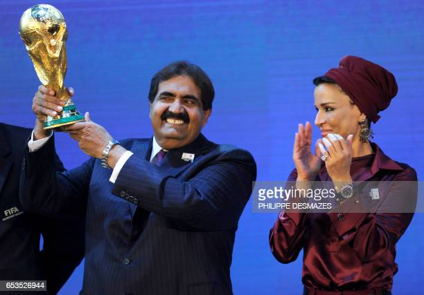 Emir of the State of Qatar Sheikh Hamad bin Khalifa AlThani poses by his wife Sheikha Moza bint Nasser AlMissned with the World Cup trophy after the...
