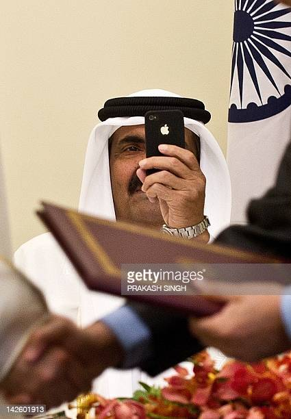 Emir of the State of Qatar Sheikh Hamad Bin Khalifa Al-Thani takes pictures with his I-phone as Indian Human Resource Development Minister Kapil...