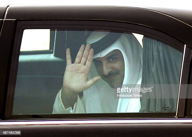 Emir of the State of Qatar Sheikh Tamim bin Hamad AlThani waves from inside of his car as he leaves from the forecourt of Rashtrapati Bhawan after...