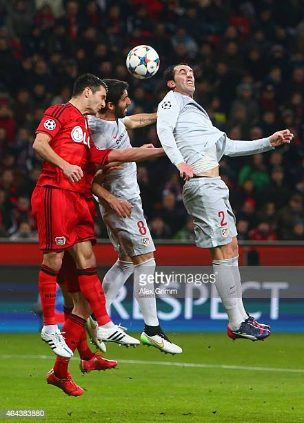 Emir Spahic of Bayer Leverkusen and Raul Garcia and Diego Godín of Atletico Madrid compete for the header during the UEFA Champions League round of...