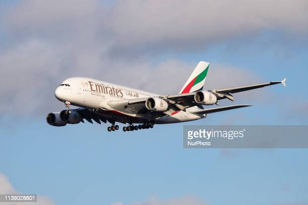 Emirates Airbus A380800 airplane with registration A6EEE landing at Amsterdam Schiphol AMS EHAM International Airport in a blue sky with clouds day...