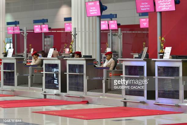 Emirates airlines checkin employees are pictured at Dubai International Airport's terminal 3 on October 10 2018