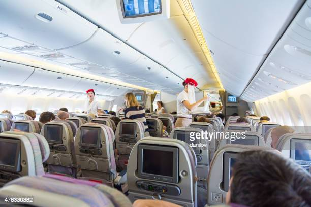 emirates cabin crew in economy class - emirates airline stock photos and pictures