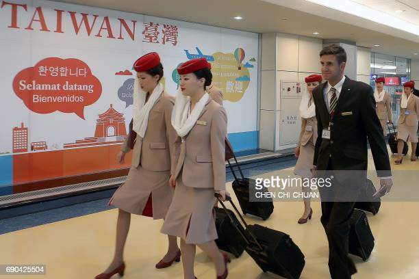 Emirates cabin crew walk past a sign at the Taoyuan international airport on May 31 2017 Emirates the Middle East's largest airline faced fierce...