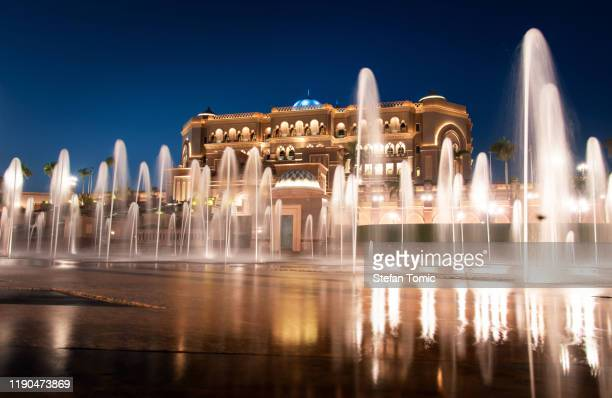 emirates palace in abu dhabi reflected on the ground level fountain - palace stock pictures, royalty-free photos & images