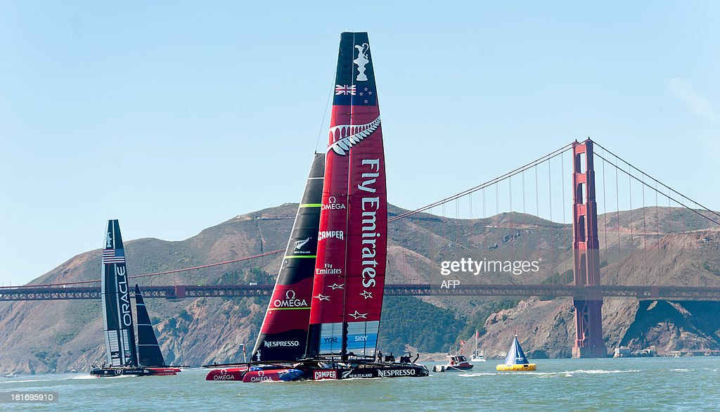 Emirates Team New Zealand (R) and Oracle Team USA (L) pass the Golden Gate Bridge while preparing for America's Cup race 16 on September 23, 2013, in San Francisco. Oracle won the race. PHOTO