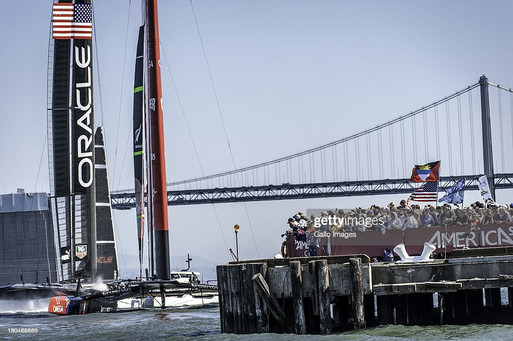 Emirates Team New Zealand and ORACLE TEAM USA sail past their fans on the end of pier 27 during day 4 of the America's Cup on September 12th, 2013 in San Francisco.