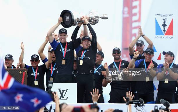 Emirates Team New Zealand helmsman Peter Burling and skipper Glenn Ashby receive the 'Auld Mug' trophy after winning the America's Cup Match...
