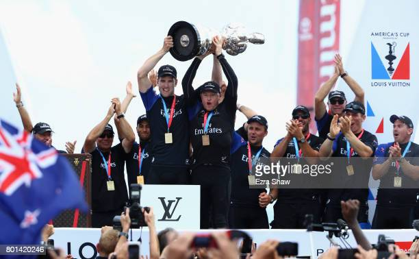 Emirates Team New Zealand helmsman Peter Burling and skipper Glenn Ashby receive the Auld Mug trophy after winning the America's Cup Match Presented...