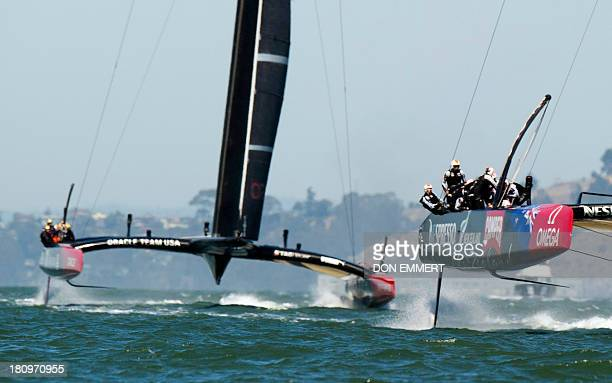 Emirates Team New Zealand leads Oracle Team USA toward the finish line in the first race of the day during the 34th America's Cup September 18 2013...
