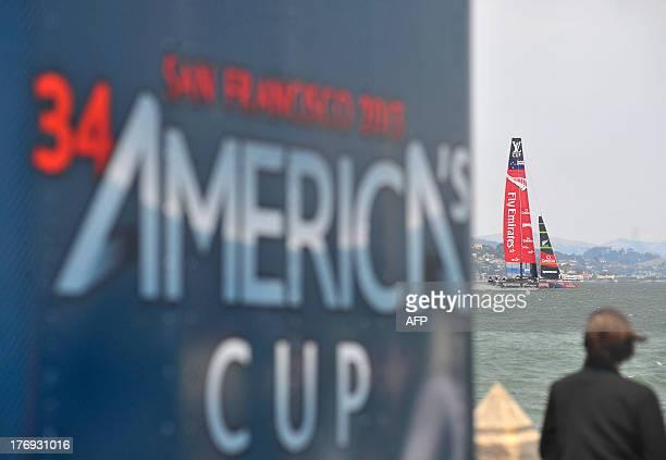 Emirates Team New Zealand sails their AC72 near a souvenir trailer during the third race of the Louis Vuitton Cup in San Francisco California on...