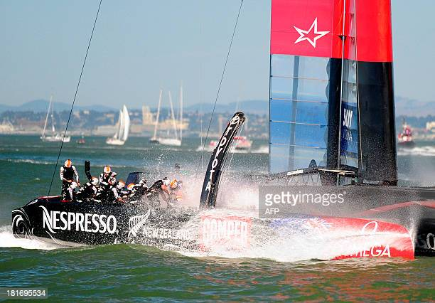 Emirates Team New Zealand splashes into the water after crossing the finish line in second place at the conclusion of race 16 of the 34th America's...