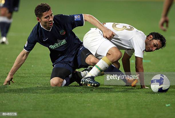 Emirati alShabab's Bader Abdulrahman tries to stop Uzbek Bunyodkor's Ulugbek Bakaev from reaching the ball during their AFC Champions League group D...