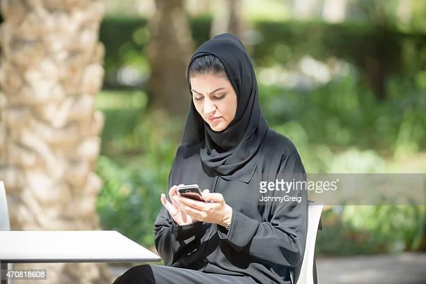Emirati arab woman in abaya texting on mobile smart phone